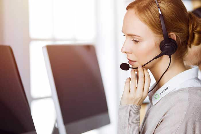 woman infront of desktop on headset at work