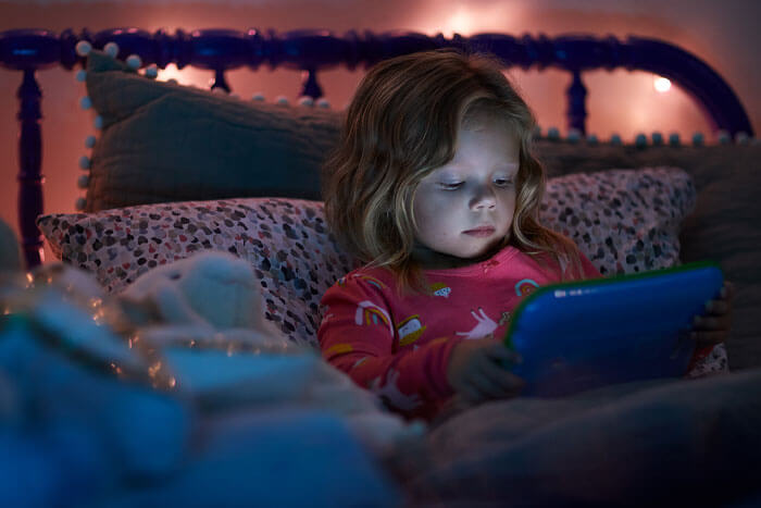 little girl on tablet at night